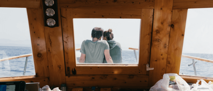 A couple is seen through the inside window sitting on the deck of their boat