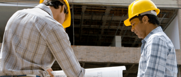 Two men on a construction site, both wearing yellow hard hats and looking at a blueprint