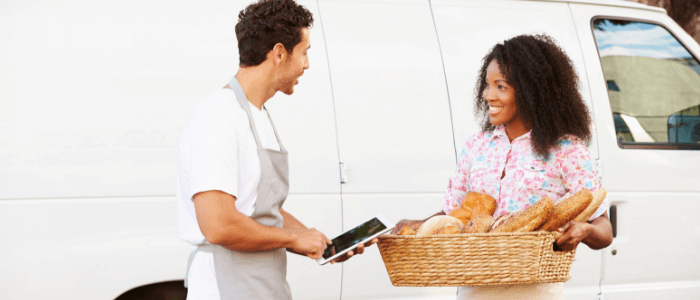 Two caterers standing outside of their van with product in their hands