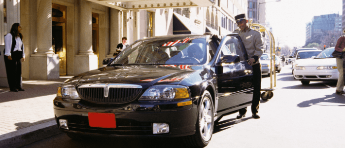 Hotel valet attendant standing by a guest's car