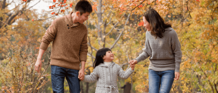 A mother, father, and young daughter walk hand in hand outside, surrounded by fall leaves