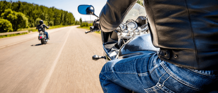 Two motorcyclists riding an open road