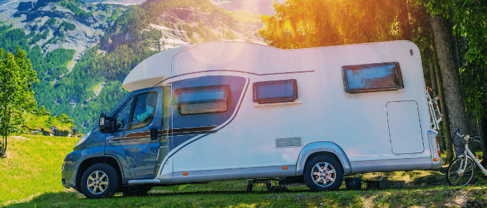 An RV sits in a clearing with the sun shining overheard and mountains in the background